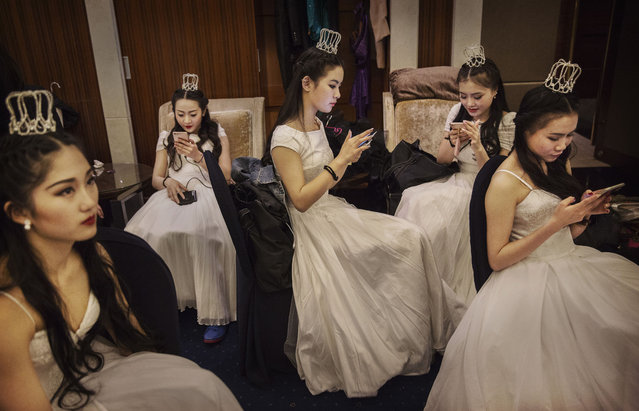 Debutantes from a local academy look at their mobile phones before taking part in the Vienna Ball at the Kempinski Hotel on March 19, 2016 in Beijing, China. (Photo by Kevin Frayer/Getty Images)