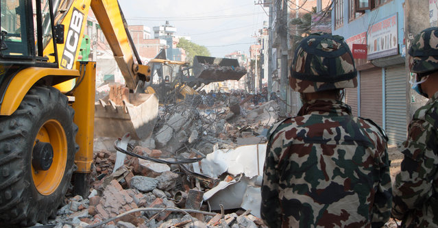 Earthmovers clear debris from the site of a building that collapsed in an earthquake in Kathmandu, Nepal, Tuesday, May 12, 2015. (Photo by Ranup Shrestha/AP Photo)