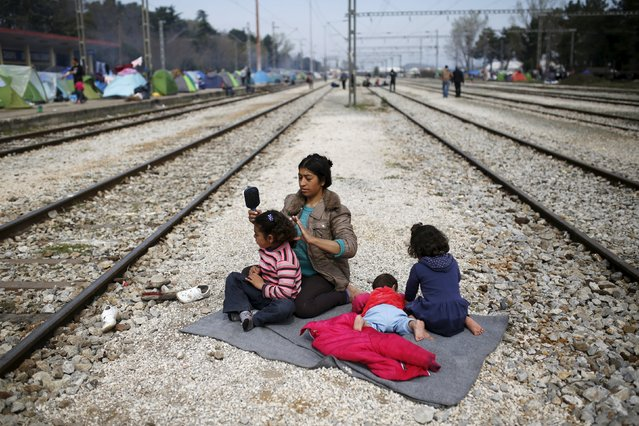 A woman sits with her children along railway tracks at a makeshift camp for migrants and refugees at the Greek-Macedonian border near the village of Idomeni, Greece, March 29, 2016. (Photo by Marko Djurica/Reuters)