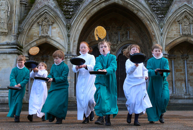 Young probationers, the trainee choristers of Salisbury Cathedral Choir, flip pancakes to mark Shrove Tuesday outside the West Front of the 13th century Cathedral on March 4, 2014 in Salisbury, England. Every year the choristers make breakfast pancakes at the Canon Precentor's house to learn about the meaning of Shrove Tuesday, which is traditionally the day that all fats and flesh are eaten up to prepare for the forty days fast of Lent. (Photo by Matt Cardy/Getty Images)