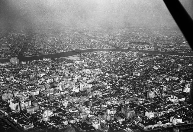An area of Tokyo, seen from the sky on August 5, 1955. Modern buildings have wiped out the scars of flattened blocks. The Sumida River flows peacefully through the Hamacho district (foreground) and the Fukawaga district. Wholesale houses and warehouses occupy most of these districts. (Photo by AP Photo via The Atlantic)