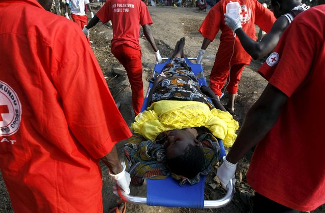 A sick Burundian refugee is carried by paramedics for treatment from her makeshift shelter on the shores of Lake Tanganyika in Kagunga village in Kigoma region in western Tanzania, as they wait for MV Liemba to transport them to Kigoma township, May 17, 2015. (Photo by Thomas Mukoya/Reuters)