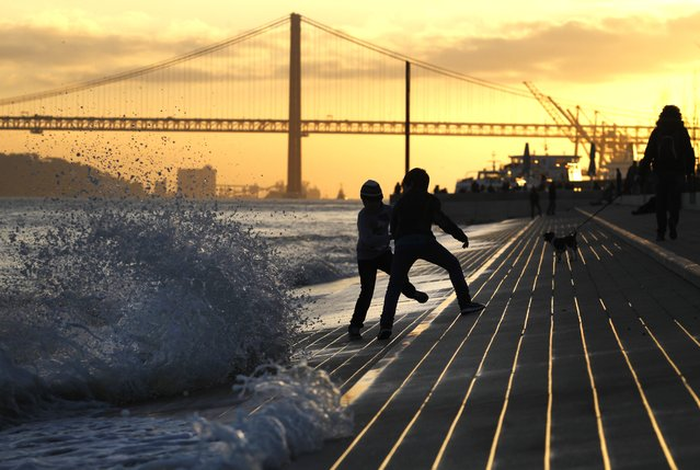 Young boys play with waves breaking at Tagus' Ribeira das Naus or Vessels Riverbank as the sun sets in Lisbon, Wednesday, March 5, 2014. (Photo by Francisco Seco/AP Photo)