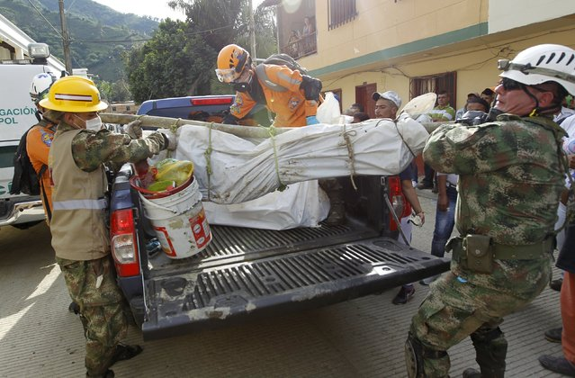 Rescue workers lift the body of a landslide victim from a truck at a cemetery, in the municipality of Salgar, in Antioquia department, May 19, 2015. (Photo by Fredy Builes/Reuters)
