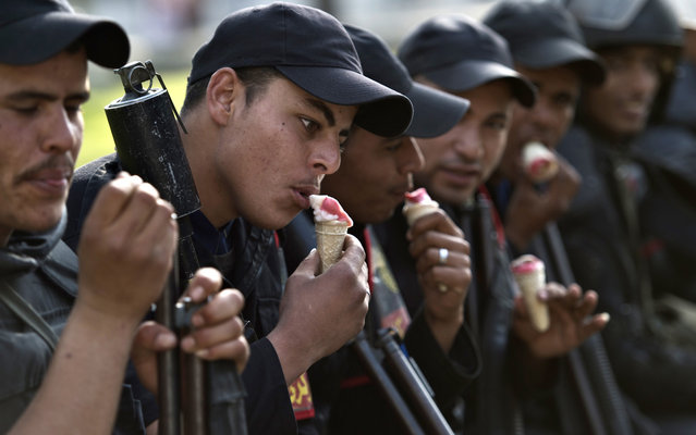 Egyptian riot police eat ice-cream as they take a break from clashes with Muslim Brotherhood students and supporters of ousted president Mohamed Morsi following a demonstration outside Cairo University on March 19, 2014. A 13-year-old boy was killed in clashes between Egyptian police and student supporters of deposed president Mohamed Morsi, state media reported, as protests resumed on campuses nationwide. (Photo by Khaled Desouki/AFP Photo)