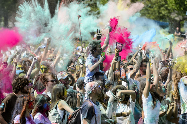Revelers throw colored powder during a Holi Festival in Yverdon-les-Bains, Switzerland, May 16, 2015. The festival is based on the Hindu Spring festival Holi, also known as the festival of colors where participants color each other with dry powder and colored water. (Photo by Jean-Christophe Bott/EPA)