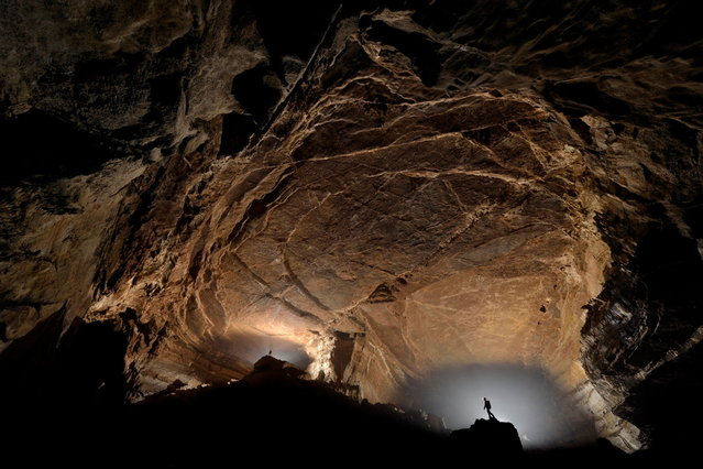 Two cave explorers are dwarfed for scale in a section of cave called Dancing Elephant Troop. Here two huge passages intercept and form a giant section of empty space, deep underground in San Wang Dong. (Photo by Robbie Shone/Caters News/ImagineChina)