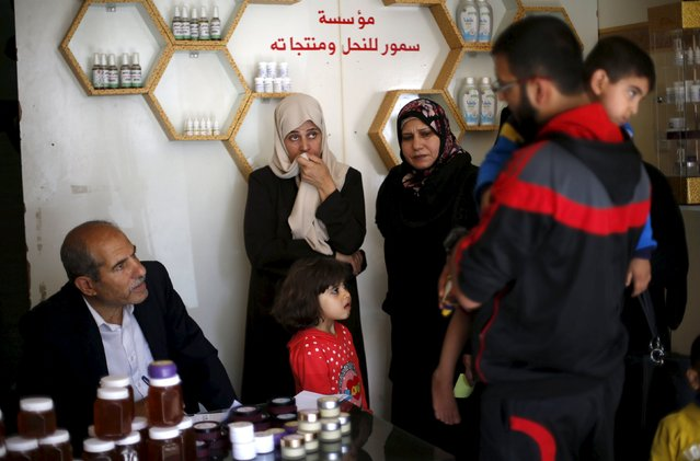 Palestinian agricultural engineer Rateb Samour (L), who treats people with bee-sting therapy, speaks with patients at his clinic in Gaza City April 11, 2016. (Photo by Suhaib Salem/Reuters)