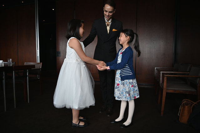 """This picture taken on June 1, 2019 shows Guillaume de Bernadac teaching children how greet each other during an etiquette and manners class in central Shanghai. De Bernadac is adamant that he is not trying to make the pupils """"more Western"""". """"Our point is really to say if you go abroad, or even within China, if you move to an international environment where you may be facing other cultures, we give you the keys to adapt"""". (Photo by Hector Retamal/AFP Photo)"""
