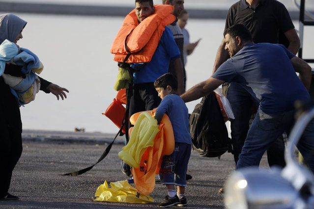 A boy holds life jackets after being picked up by the Greek coast guard at the port of Mitylene, on the northeast Greek island of Lesvos on Wednesday, June 17, 2015. Around 100,000 migrants have entered Europe so far this year as Italy and Greece have borne the brunt of the surge with many more migrants expected to arrive from June through to September. (AP Photo/Thanassis Stavrakis