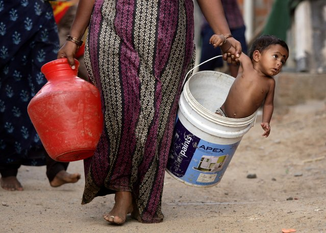A woman carries her son in a bucket after collecting water from a municipal water tanker on the outskirts of Chennai, India, July 4, 2019. (Photo by P. Ravikumar/Reuters)