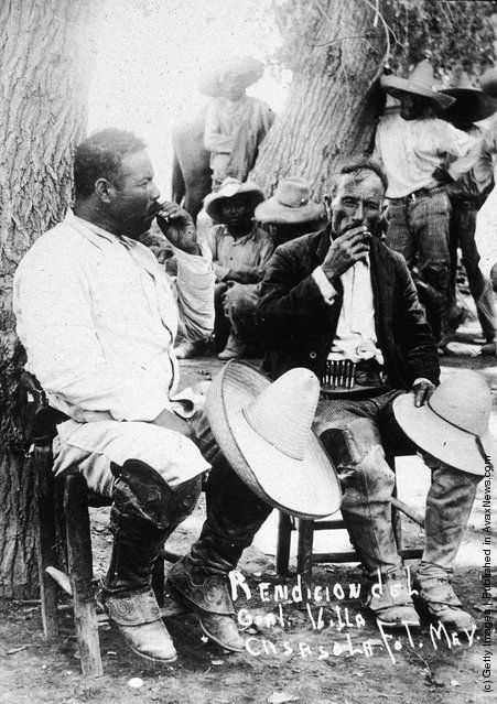 Mexican revolutionary leader Pancho Villa sits against a tree with a fellow soldier, their straw hats over their knees, following the Mexican Revolution of 1911
