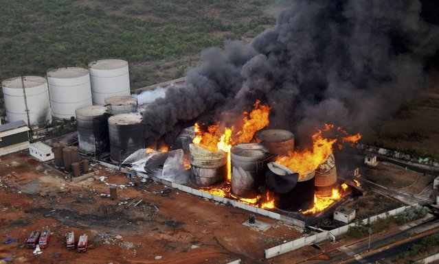 Flames rise and black smoke fills the air after a fire broke out at the Biomax Fuels Ltd. near Vishakhapatnam, a port city in Andhra Pradesh state, India, Wednesday, April 27, 2016. The biofuel manufacturing plant caught fire Tuesday night, triggering explosions in biodiesel tanks and forcing around 150 workers to flee the facility, officials said Wednesday. (Photo by Press Trust of India via AP Photo)