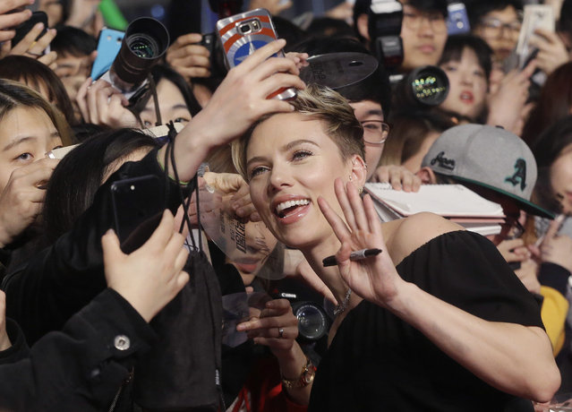 """Actress Scarlett Johansson poses with fans for a selfie during a promotional event for her latest film """"Ghost in the Shell"""" in Seoul, South Korea, Friday, March 17, 2017. The film will be released in South Korea on March 29. (Photo by Ahn Young-joon/AP Photo)"""