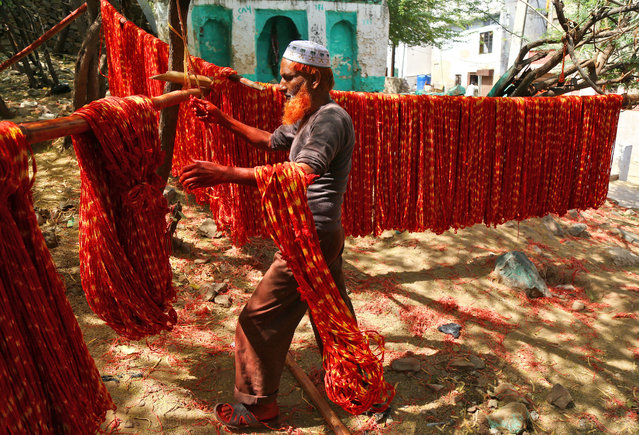 """A worker hangs """"Kalavas"""" or sacred threads to dry after dyeing them with colours in Ajmer, India, March 17, 2017. (Photo by Himanshu Sharma/Reuters)"""