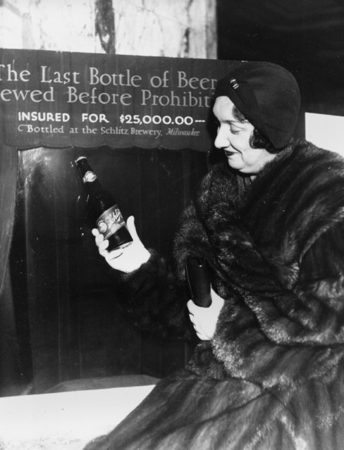Rae Samuels holds the last bottle of beer that was distilled before prohibition went into effect in Chicago, Ill., December 29, 1930.  The bottle of Schlitz has been insured for $25,000. (Photo by AP Photo)