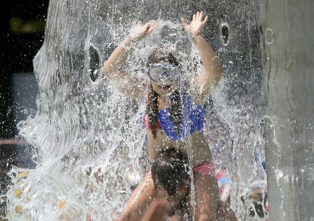 A girl plays in the waterfall at the the fun bath in Endenich, a suburb of Bonn, western Germany, July 3, 2015. A widespread, long-lasting heat wave will spread across much of France, U.K., Belgium, the Netherlands and western Germany with forecast highs on Wednesday reaching 35 degrees Celsius (95 degrees Fahrenheit). (Photo by Wolfgang Rattay/Reuters)