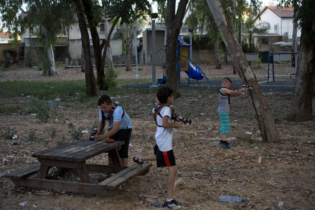 In this Monday, June 22, 2015, photo, Israeli youth play with laser guns in the southern Israeli town of Sderot, next to the Israel-Gaza border. (Photo by Oded Balilty/AP Photo)