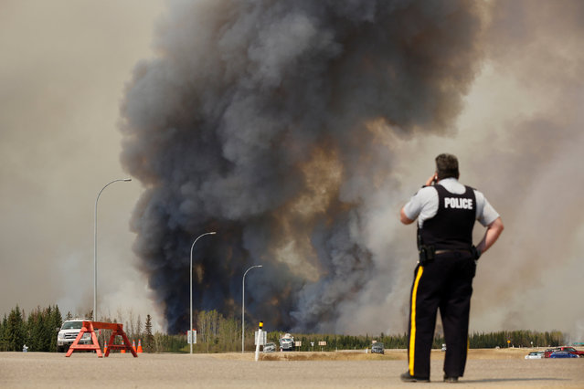 A Royal Canadian Mounted Police officer looks on at smoke rises from wildfires near Fort McMurray, Alberta, Canada, May 6, 2016. (Photo by Chris Wattie/Reuters)