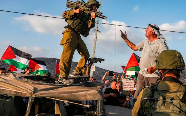 A Palestinian protester yells at an Israeli soldier as he confronts him atop an Israeli army vehicle during a protest against Israeli forces conducting an exercise in a residential area near the Palestinian village of Naqura, northwest of Nablus in the occupied West Bank, on September 4, 2019. (Photo by Jaafar Ashtiyeh/AFP Photo)