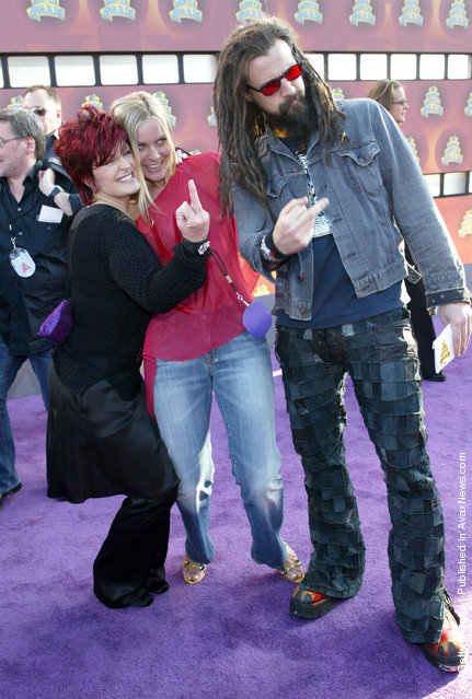 The Osbournes star Sharon Osbourne (L) and musician, Rob Zombie, flip the finger as Zombie's wife looks on at the 2002 MTV Movie Awards at The Shrine Auditorium