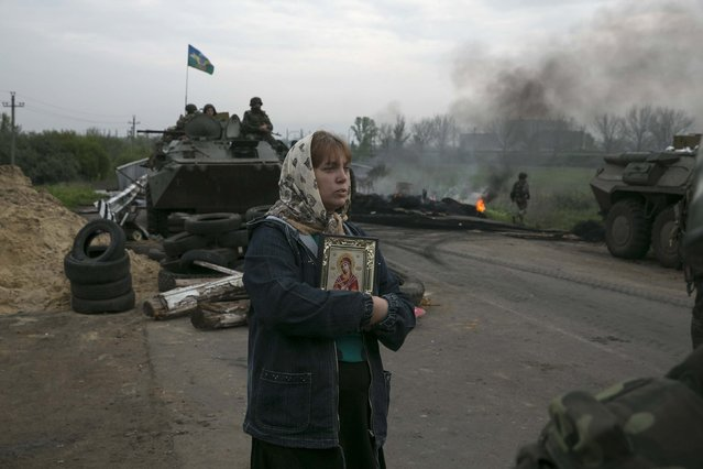 A woman stands with an Orthodox icon at a Ukrainian checkpoint near the town of Slaviansk in eastern Ukraine May 2, 2014. (Photo by Baz Ratner/Reuters)