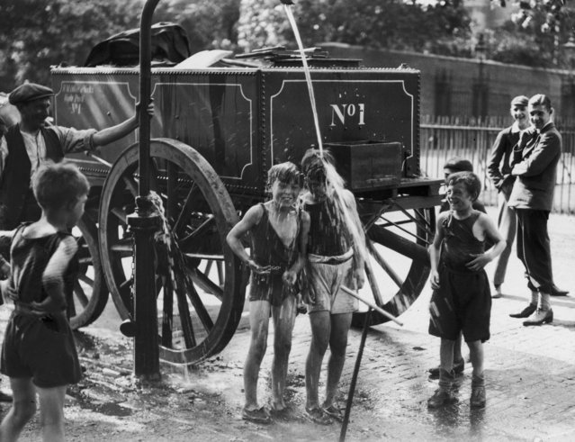 A water cart man turns the water main on a group of boys to help them cool off in a street in Westminster, London on August 1930 during a heatwave. (Photo by Fox Photos/Getty Images)