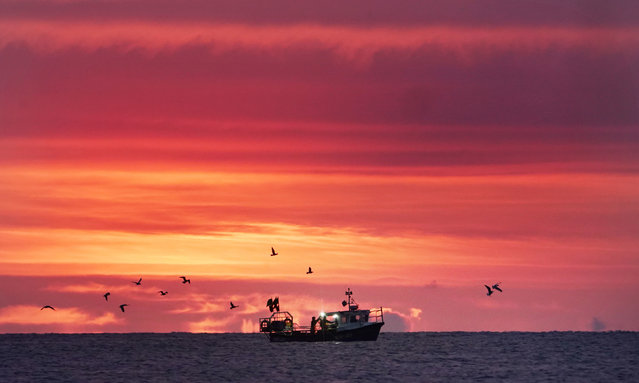 The sun rises over the sea as a small fishng boat collects Lobster pots off the coast of Whitley Bay on August 14, 2019, before more rain and thunderstorms are due to hit parts of Britain today. (Photo by Owen Humphreys/PA Images via Getty Images)