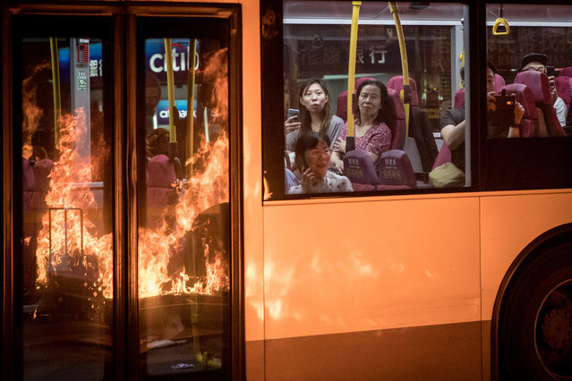 "Flames from a burning barricade lit by pro-democracy protesters is reflected in the windows of a passing bus as passengers watch on during a protest gathering in front of Mong Kok police station on September 22, 2019 in Hong Kong, China. Pro-democracy protesters have continued demonstrations across Hong Kong, calling for the city's Chief Executive Carrie Lam to immediately meet the rest of their demands, including an independent inquiry into police brutality, the retraction of the word ""riot"" to describe the rallies, and genuine universal suffrage, as the territory faces a leadership crisis. (Photo by Chris McGrath/Getty Images)"