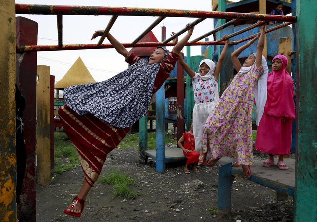 Muslim children play on monkey bars after their morning prayer at a park in a slum area in Tondo, metro Manila July 17, 2015. Muslims all over the world celebrate Eid al-Fitr as the holy month of Ramadan comes to an end on Friday. (Photo by Romeo Ranoco/Reuters)