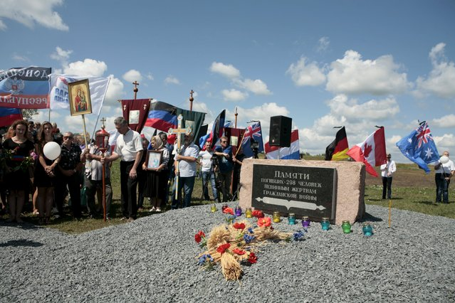People take part in a commemoration ceremony at the site of the Malaysia Airlines flight MH17 plane crash near the village of Hrabove in Donetsk region, Ukraine, July 17, 2015. (Photo by Kazbek Basaev/Reuters)