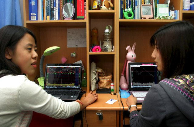 Students sit in front of laptop screens showing stock information at their dormitory, in Beijing, November 6, 2007. China's government may be rattled by the wild plunge in stock prices over the past month, but for many of the country's students, it's just another exercise to get ready for life in the real world. (Photo by Reuters/Stringer)