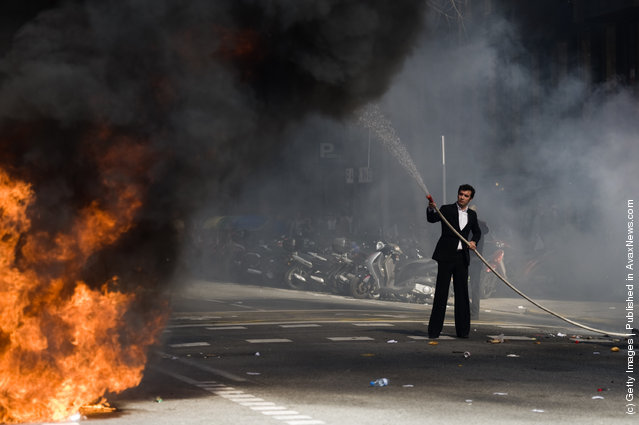 A hotel receptionist tries to put out a fire  during a demonstration on February 29, 2012 in Barcelona