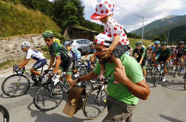 A cycling supporter cheers the pack of riders with Movistar rider Nairo Quintana of Colombia (L) as they climb during the 161-km (100 miles) 17th stage of the 102nd Tour de France cycling race from Digne-les-Bains to Pra Loup in the French Alps mountains, France, July 22, 2015. (Photo by Stefano Rellandini/Reuters)