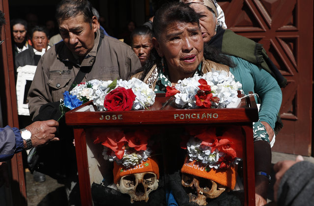 """A woman carries decorated human skulls after praying in the chapel at the General Cemetery during the """"Natitas"""" festival in La Paz, Bolivia, Friday, November 8, 2019. The skulls, called """"natitas"""", which means """"without a nose"""" in the indigenous Aymara language, are cared for and decorated by faithful who use them as amulets, believing they serve as protection. The tradition marks the end of the Catholic All Saints holiday, but is not recognized by the Catholic church. (Photo by Juan Karita/AP Photo)"""