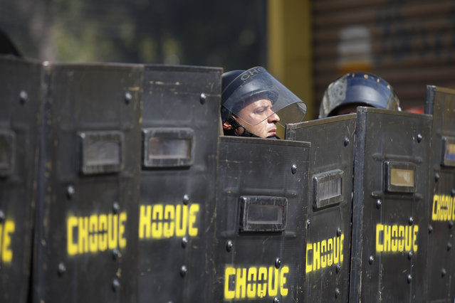A Brazilian riot policeman looks up from behind his shield after clashes erupted in Sao Paulo, Brazil, Thursday, June 12, 2014. More than 300 demonstrators gathered along a main highway leading to the stadium. Some in the crowd tried to block traffic, but police repeatedly pushed them back, firing canisters of tear gas and using stun grenades. (Photo by Dario Lopez-Mills/AP Photo)