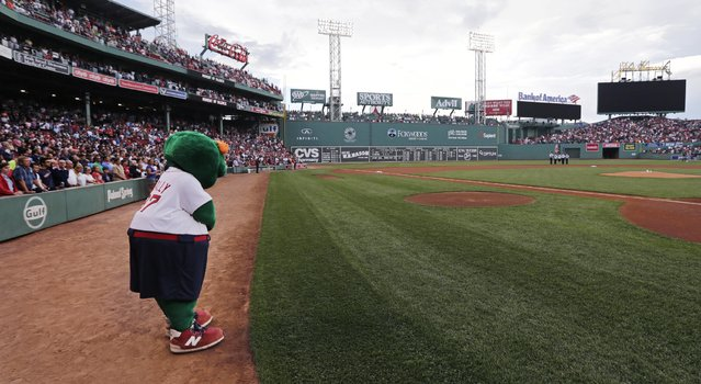 Wally the Green Monster, the Boston Red Sox's mascot, and fans pause for a moment of silence for shooting victims at a Louisiana theater and Tennessee military recruiting station prior to a baseball game at Fenway Park in Boston, Friday, July 24, 2015. (Photo by Charles Krupa/AP Photo)
