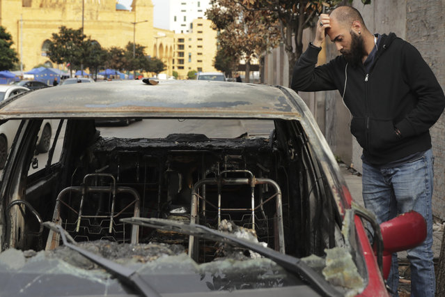 A man inspects the remains of a burned car that was destroyed during clashes between rival groups in Beirut, Lebanon, Monday, November 25, 2019. A key road in the Lebanese capital reopened Monday following clashes throughout the night between rival groups, some of the worst violence since protests against the country's ruling elite began last month. (Photo by Hassan Ammar/AP Photo)