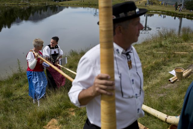 Alpenhorn players chat amongst themselves along the Lac de Tracouet, situated 2200 meters (7220 feet) above sea level in Haute-Nendaz, canton of Valais, Switzerland, Sunday, July 26, 2015. (Photo by David Azia/AP Photo)