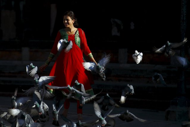 A devotee chases pigeons during the Shrawan Sombar festival at Pashupatinath temple in Kathmandu, July 27, 2015. The festival lasts for a month, during which devotees fast and worship Lord Shiva to pray for happiness for their families. (Photo by Navesh Chitrakar/Reuters)
