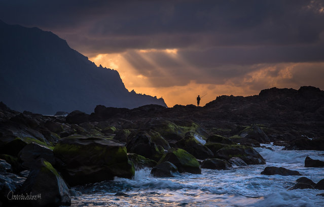 """""""The lone fisher"""". This dramatic light showed up shortly at Benijo Beach (Tenerife/Spain). The lonely fisherman adds a special something in this one. My personal favourite from our journey in spring 2014. The weather wasn´t always good, but I prefer clouds instead of a bright shining blue sky :). Photo location: Benijo Beach,  Tenerife, Spain. (Photo and caption by Christiano Schwedano/National Geographic Photo Contest)"""