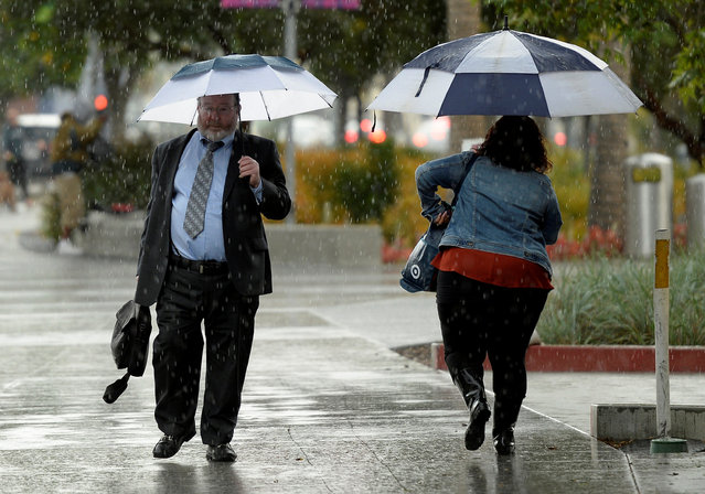Pedestrians navigate through light rain as they make their way through it in downtown Los Angeles, California, May 6, 2016. (Photo by Kevork Djansezian/Reuters)