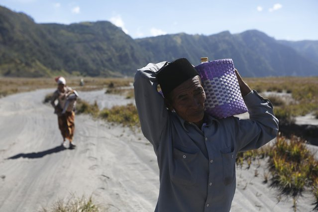 Hindu villagers carry their offering as they walk to collect holy water from a stream for prayers ahead of the annual Kasada festival at Mount Bromo in Indonesia's East Java province, July 31, 2015. (Photo by Reuters/Beawiharta)