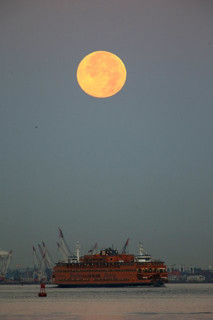 A full moon, known as the Blue Moon,  is seen over the Staten Island Ferry while it makes its way to New York July 31, 2015. (Photo by Eduardo Munoz/Reuters)