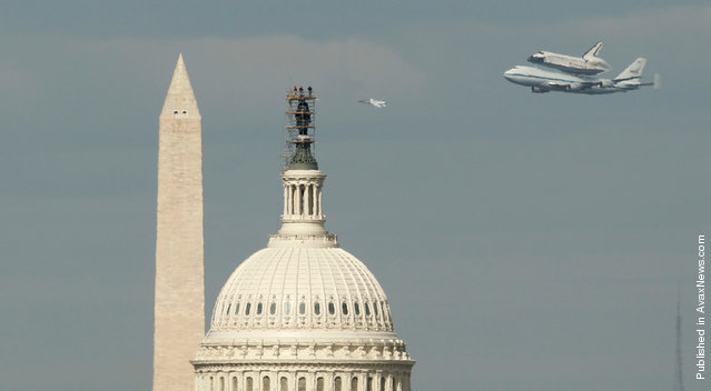 Spectators atop the U.S. Capitol Building watch as Discovery and a a NASA T-38 aircraft fly past the Washington Monument, on April 17, 2012