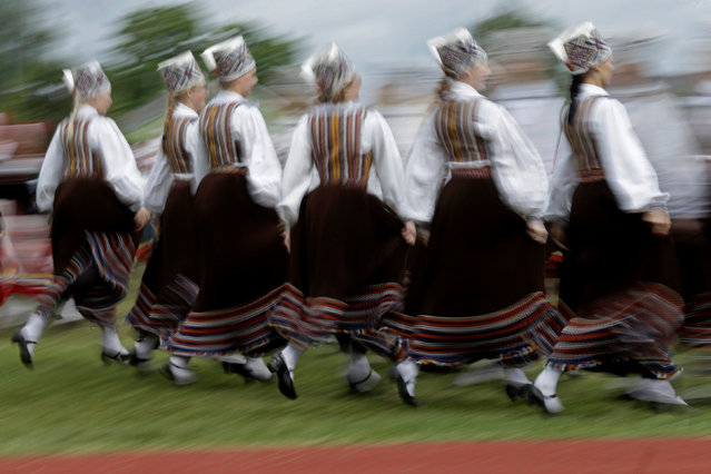 Dancers wear traditional dresses as they perform during women's dance festival in Jogeva, Estonia, June 12, 2016. (Photo by Ints Kalnins/Reuters)
