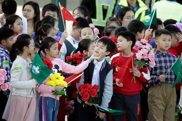 Children holding Chinese and Macau flags get ready before Chinese President Xi Jinping's arrival at Macau International Airport in Macau, China December 18, 2019, ahead of the 20th anniversary of the former Portuguese colony's return to China. (Photo by Jason Lee/Reuters)