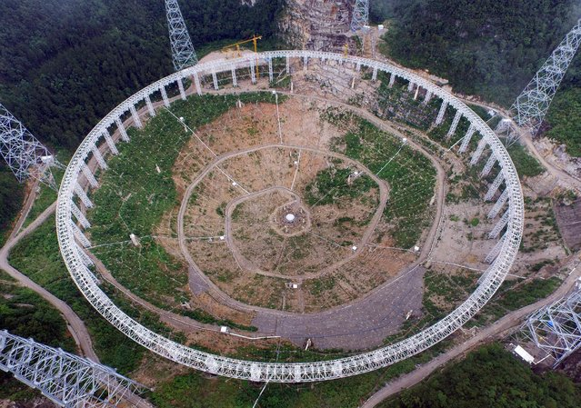 A 500 meter aperture spherical telescope (FAST) is seen in construction in Pingtang county, Guizhou province, July 28, 2015. According to local media, the telescope will be put into use by September, 2016 and will become the largest in the world. China invested 667 million yuan in the construction and only the site selection took 15 years. (Photo by Reuters/Stringer)