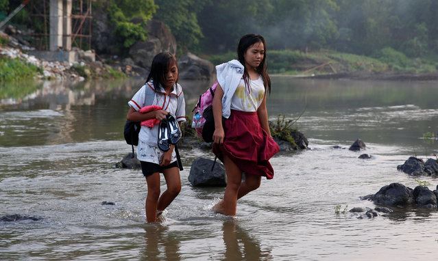 Girls walk on a shallow river to attend the opening of classes at a remote Casili Elementary School in Montalban, Rizal northeast of Manila, Philippines June 13, 2016. (Photo by Erik De Castro/Reuters)