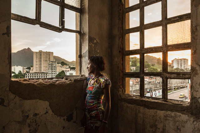 Planned improvements to Rio's favelas have meant increases in rent, forcing the poorest families into squatting in unoccupied buildings. Photographer Tariq Zaidi visits the Mangueira community favela, less than 1km from the showpiece Maracanã stadium, to see what life is like for the women living there. Here: A woman stands at the windows of the abandoned ministry of finance building in the Mangueira favela in Rio de Janeiro's North Zone. (Photo by Tariq Zaidi/The Guardian)